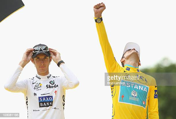 Andy Schleck of team Saxo Bank, who finished 2nd overall, looks on as Alberto Contador of team Astana celebrates on the podium after the twentieth...