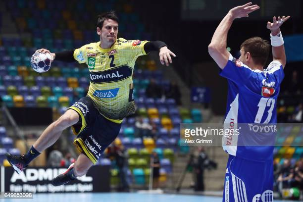Andy Schmid of RheinNeckar Loewen is challenged by Szergej Gorbok of Szeged during the EHF Champions League match between Rhein Neckar Loewen and...