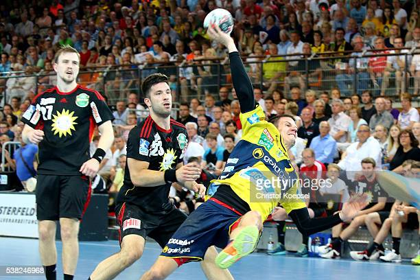 Andy Schmid of RN Loewen scores a goal against Tim Suton of TuS N-Luebbecke during the DKB Handball Bundesliga match between TuS N-Luebbecke and RN...