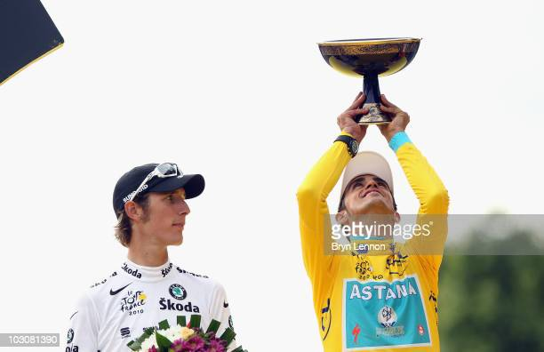 Andy Shleck of team Saxo Bank looks on as Alberto Contador of team Astana celebrates victory after the twentieth and final stage of Le Tour de France...