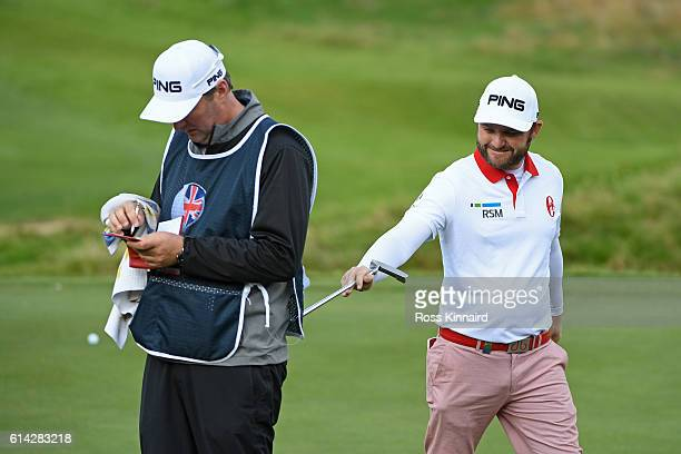Andy Sullivan of England pokes his caddy with his putter on the second green during the first round of the British Masters at The Grove on October 13...