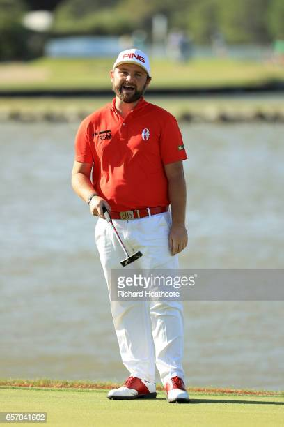Andy Sullivan of England reacts after his putt is blown by the wind on the 13th hole of his match during round two of the World Golf...