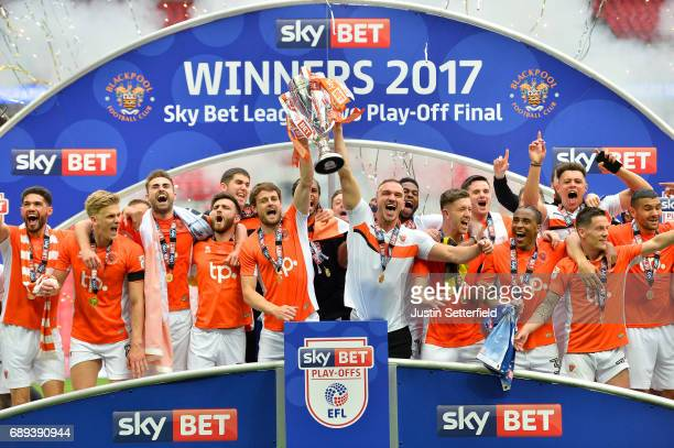 Andy Taylor and Tom Aldred of Blackpool hold the trophy as they celebrate victory and promotion with team mates after the Sky Bet League Two Playoff...
