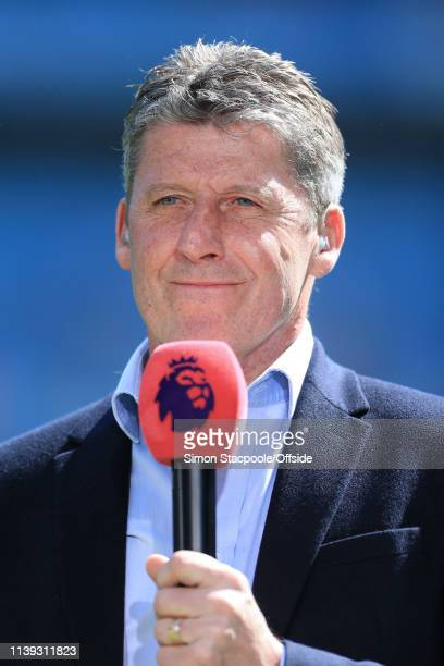 Andy Townsend holds the microphone as he works as a pitchside television pundit during the Premier League match between Manchester City and Tottenham...