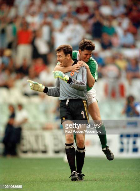 Andy Townsend of the Republic of Ireland celebrates by jumping on the back of goalkeeper Packie Bonner after the 1990 FIFA World Cup 2nd Round match...