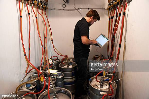 Andy Troxel SteadyServ Technologies checks newly installed RFID tags on kegs at the Crazy Mountain Brewery June 09 2016 The scale is part of the...