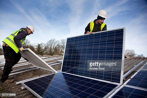 Andy Tyrrell and Jake Beautyman install solar panels on a barn roof on Grange farm near Balcombe The installation is part of an initiative by local...