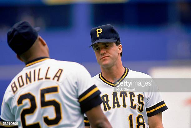 Andy Van Slyke of the Pittsburgh Pirates talks with teammabte Bobby Bonilla during a 1990 MLB season game at Three Rivers Stadium in Pittsburgh,...
