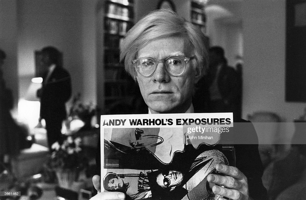 Andy Warhol (1926 - 1987), American pop artist and filmmaker, holding an example of one of his posters. Original Publication: People Disc - HM0195