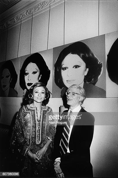 Andy Warhol and Iran's Shabanou Farah Palhavi also known as Empress Farah Diba in front of a screen print portrait by Warhol during a reception at...