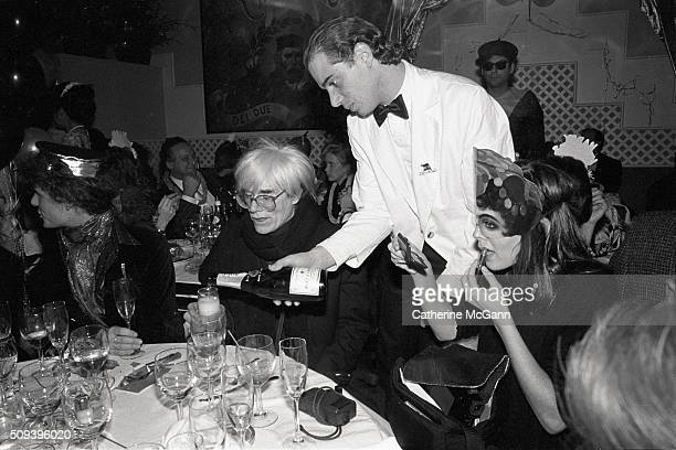 Andy Warhol celebrates his last New Year's Eve as a waiter pours champagne during a dinner at Cafe Roma restaurant in New York City New York on...