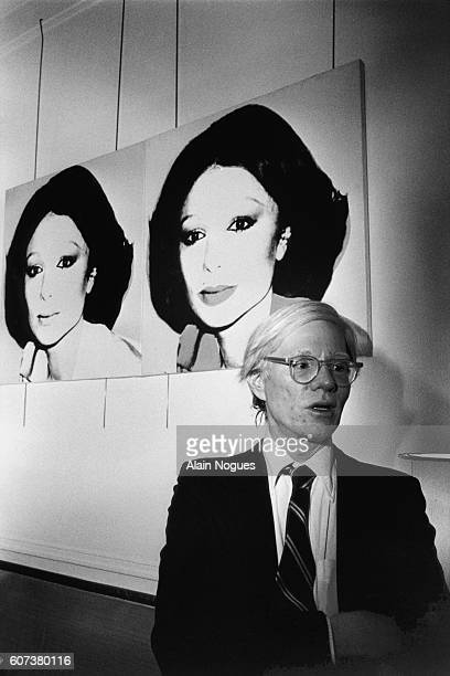 Andy Warhol in front of his screen print portrait of Iran's Shabanou Farah Palhavi also known as Empress Farah Diba during a reception at the Waldorf...