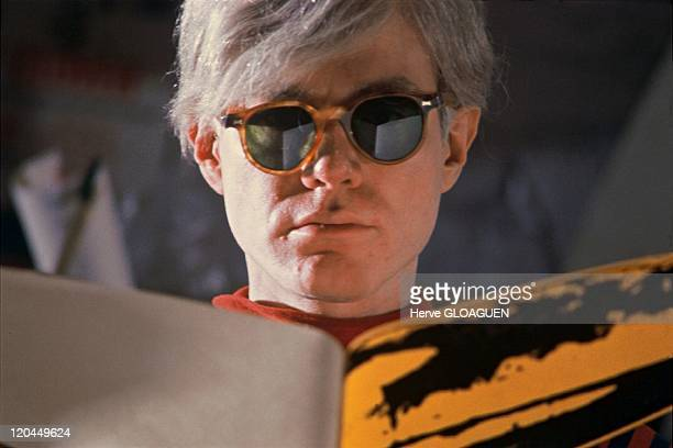 Andy Warhol in New York, United States in 1966 - Andy Warhol at the Factory, he tears a huge banana plastic before fixing it on the paper.