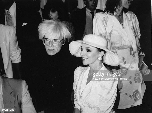 Andy Warhol interviews Joan Collins for his magazine Interview during the showing of her fashions at Stringfellows This is one of the last photos of...