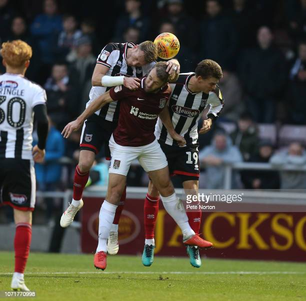 Andy Williams of Northampton Town contests the ball with Andrew Fox and Danny Collins of Grimsby Town during the Sky Bet League Two match between...