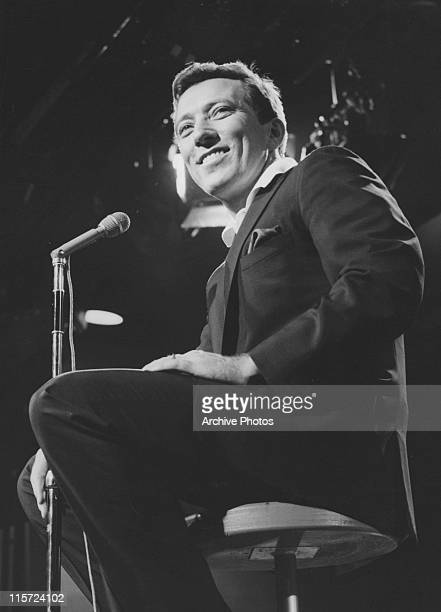 Andy Williams US singer sits smiling beside a microphone in a publicity still issued for his television show 'The Andy Williams Show' USA 1966
