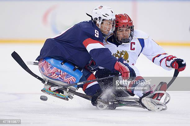 Andy Yohe of the United States and Dmitrii Lisov of Russia battle for the puck during the Ice Sledge Hockey Preliminary Round Group B match between...