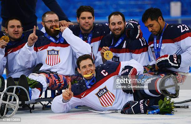 Andy Yohe of the United States poses with team mates after winning the gold medal in the Ice Sledge Hockey Gold Medal game between the United States...