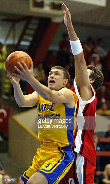 Andziy Lebedev from Ukraine tries to hold on to the ball while under pressure from Mehmet Okur from Turkey during their match in group D of the FIBA...