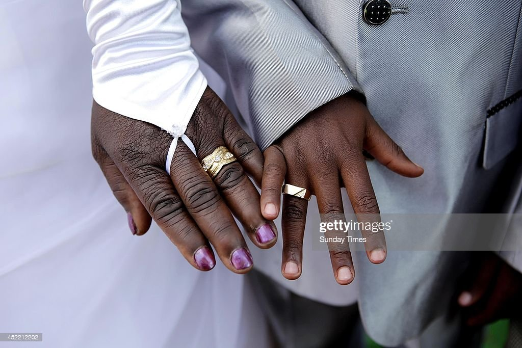 anele Masilela, a nine year-old watches as his wife Helen Shabangu, 62 year-old kisses her 'real life' husband Abel, at their white wedding on July 12, 2014 in Bushbuckridge, South Africa. Sanele who married Helen last year in a bid to appease his ancestors, repeated the ceremony this year. The wedding was arranged after Sanele was tormented by his late grandfather, Busy Masilela and other ancestral spirits. Sanele's mother explained to guests that Busy had never been married and he wanted his grandson to do so to appease the spirits.