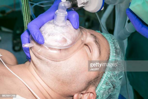 Anesthesiologist holding oxygen mask over patient during surgery
