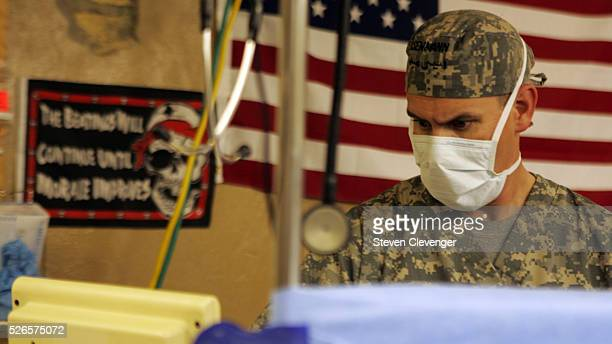 Anesthetist Captain Ray Eisennman watces the levels on his machinery during the operation on a civilian Afghan. The Afghan's story was that he had...