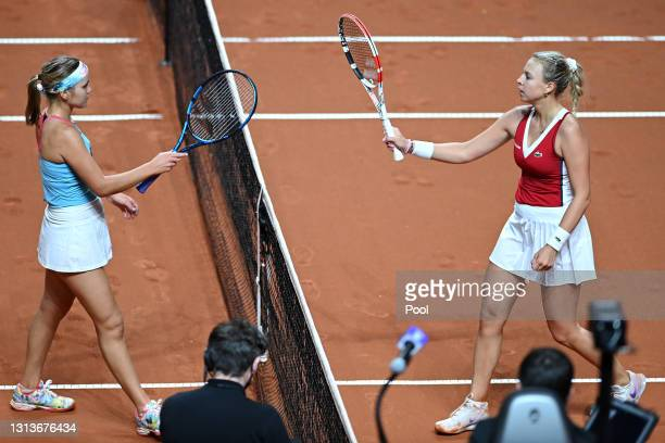 Anett Kontaveit of Estonia celebrates winning match point as she touches racquets with Sofia Kenin on day 5 of the Porsche Tennis Grand Prix match...