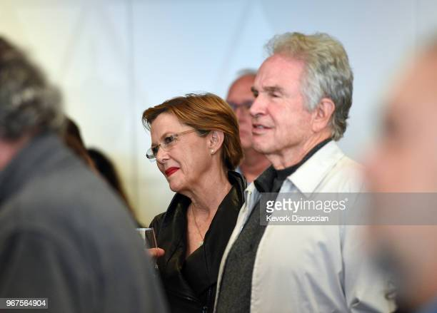 Anette Bening and Warren Beatty listen to George Stevens Jr filmmaker and founder of the American Film Institute speak during a reception in...