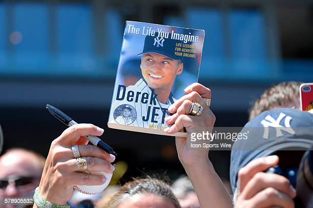 ANew York Yankees fan holds up a sharpie and a New York Yankees shortstop Derek Jeter book for him to sign in action during a game between the...