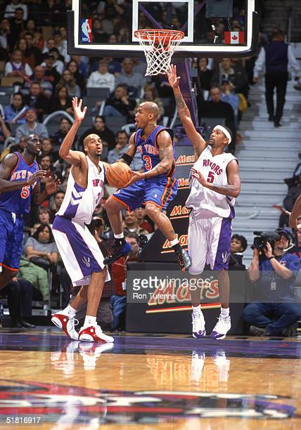 Anfernee Hardaway of the New York Knicks goes up for the basket between Loren Woods and Jalen Rose of the Toronto Raptors at Air Canada Centre on...