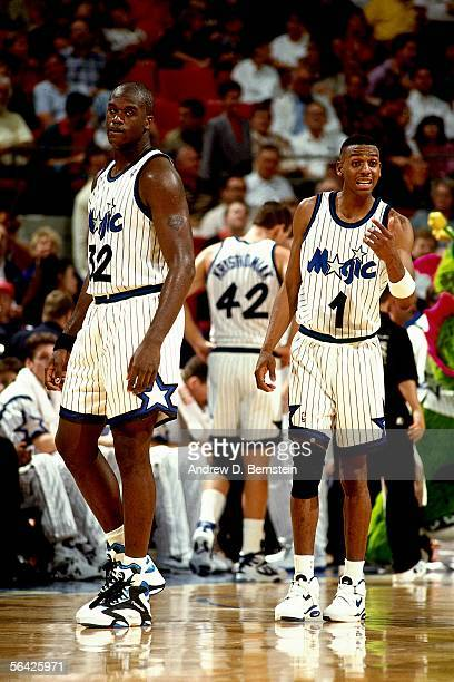 Anfernee Hardaway of the Orlando Magic receives the play from bench as teammate Shaquille O'Neal of the Orlando Magic looks on during an NBA game at...