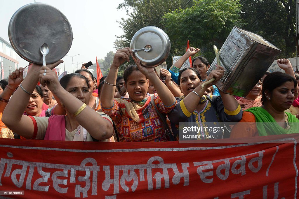 Anganwadi workers shout slogans and wave utensils as they march towards the residence of Cabinet Minister Bikram Singh Majithia during a protest...
