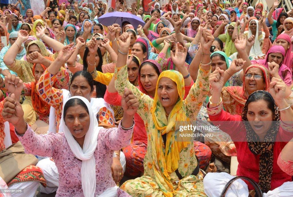Anganwadi workers shout slogans as they sit outside the residence of Rajya Sabha MP and Bharatiya Janata Party Punjab president Shwait Malik during a.