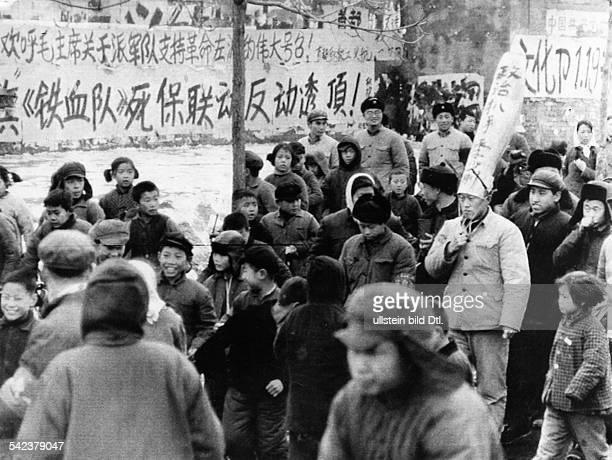 Angehörige der Roten Garden führen einen Staatsbeamten mit einem Schandhut durch die Strassen Pekings Dem Träger wird vorgeworfen ein 'politischer...