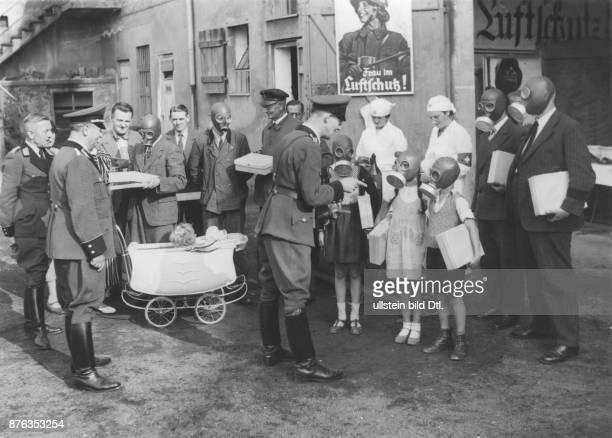 Angehörige des Reichsluftschutzbundes verteilen Gasmasken an Kinder und Erwachsene 1937