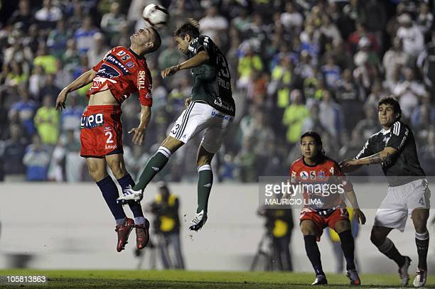Angel Aguirre , of Bolivia's Universitario de Sucre, vies with Danilo, of Brazil's Palmeiras, as Marvin Bejarano and Fabricio look on during their...