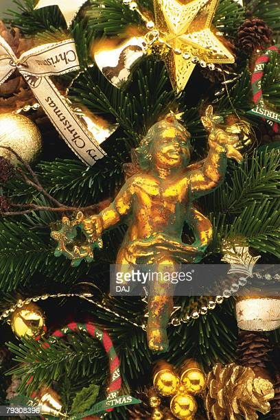 Angel and Christmas ornaments on Christmas tree, front view, close up