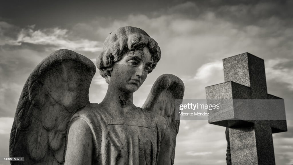 Angel and cross in the cemetery : Stock Photo