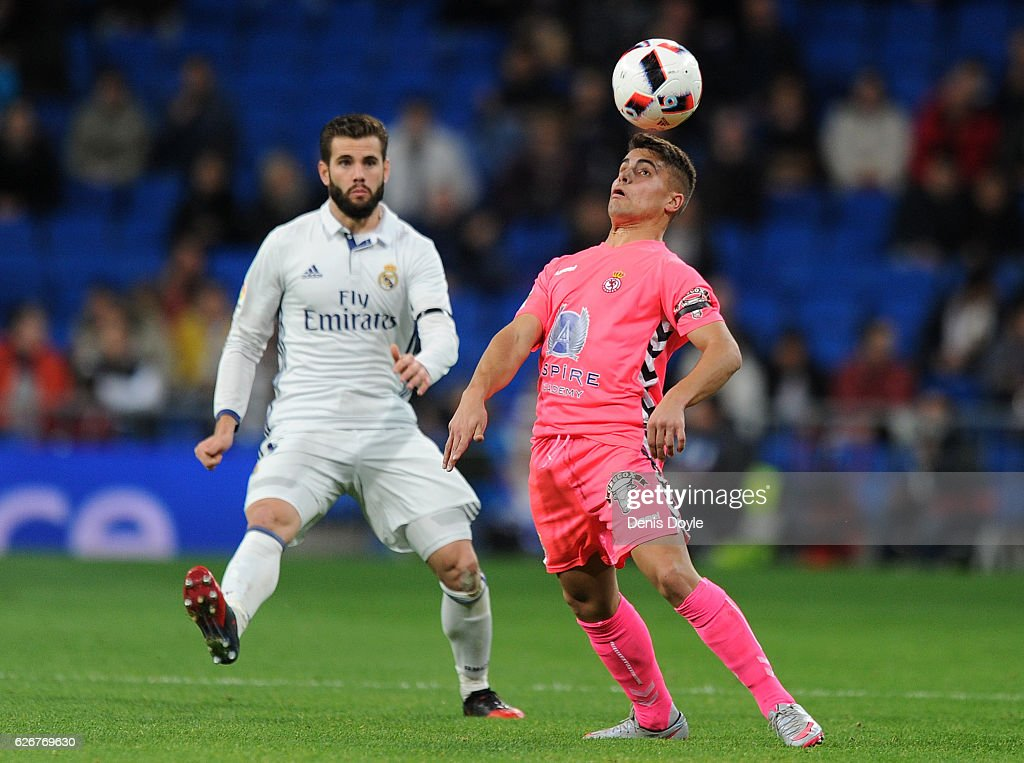 Angel Bastos of Cultural Leonesa balances the ball on his head in front of Nacho of Real Madrid CF during the Copa del Rey last of 32 match between Real Madrid and Cultural Leonesa at estadio Santiago Bernabeu on November 30, 2016 in Madrid, Spain.