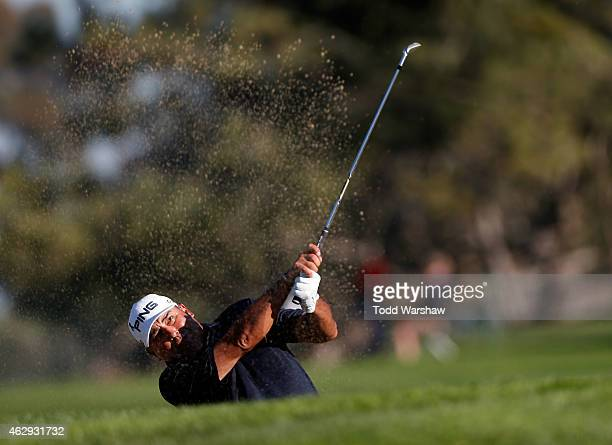 Angel Cabrera of Argentina plays a shot out of the bunker on the fourth hole during the third round of the Farmers Insurance Open at Torrey Pines...
