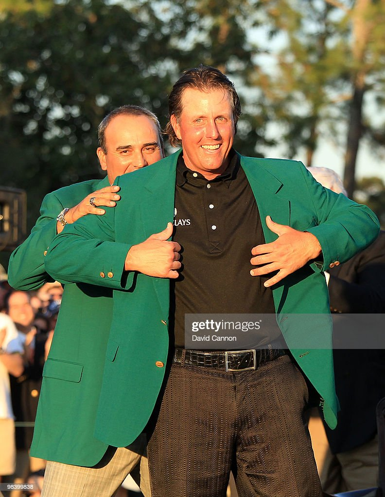 Angel Cabrera of Argentina presents Phil Mickelson with the green jacket during the green jacket presentation after the final round of the 2010 Masters Tournament at Augusta National Golf Club on April 11, 2010 in Augusta, Georgia.