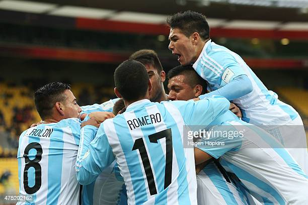 Angel Correa of Argentina is swamped by his teammates while celebrating his goal during the Group B FIFA U20 World Cup New Zealand 2015 match between...