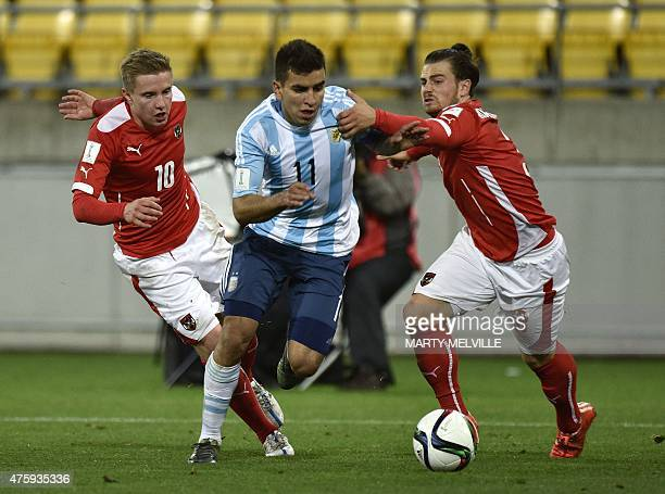 Angel Correa of Argentina is tackled by Markus Blutsch and Daniel Rosenbichler of Austria during the FIFA Under20 World Cup football match between...