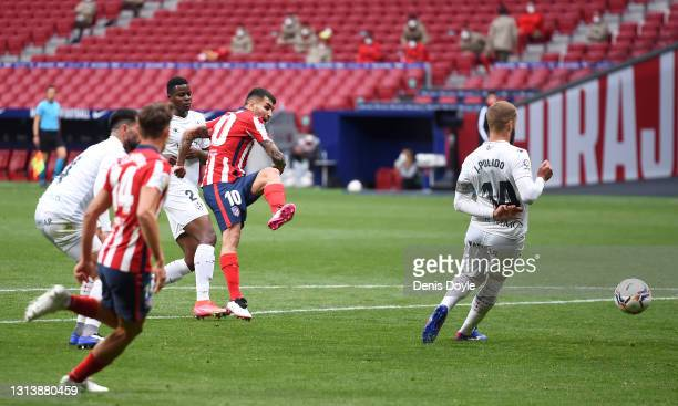 Angel Correa of Atletico de Madrid scores their sides first goal whilst under pressure from Jorge Pulido of SD Huesca during the La Liga Santander...