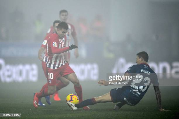Angel Correa of Atletico Madrid battles for possession with Damian Musto of SD Huesca during the La Liga match between SD Huesca and Club Atletico de...