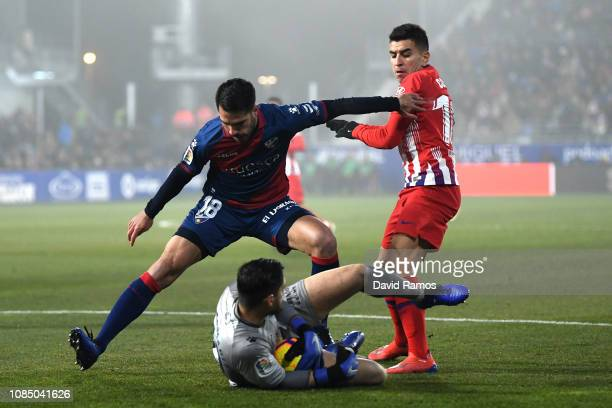 Angel Correa of Atletico Madrid battles for possession with Pablo Insua and Roberto Santamaria of SD Huesca during the La Liga match between SD...