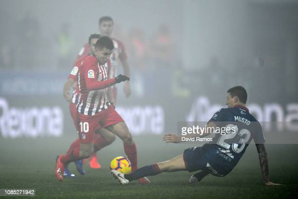 Angel Correa of Atletico Madrid is challenged by Damian Musto of SD Huesca during the La Liga match between SD Huesca and Club Atletico de Madrid at...