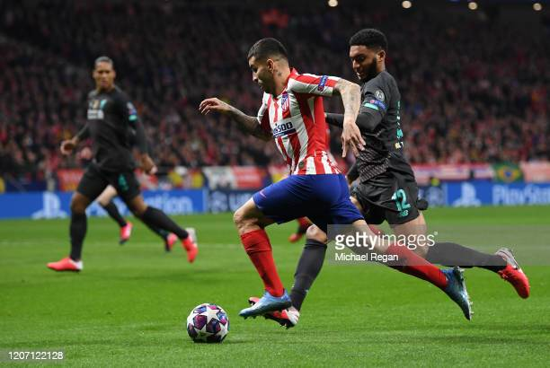 Angel Correa of Atletico Madrid is challenged by Joe Gomez of Liverpool during the UEFA Champions League round of 16 first leg match between Atletico...