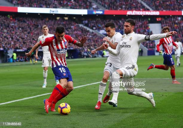 Angel Correa of Atletico Madrid is faced by Sergio Ramos and Sergio Reguilon of Real Madrid during the La Liga match between Club Atletico de Madrid...