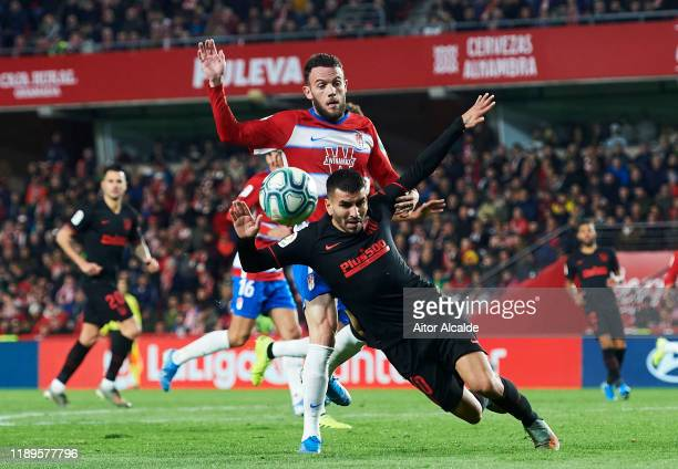 Angel Correa of Club Atletico de Madrid duels for the ball with Joaquin Marin 'Quini' of Granada CF during the Liga match between Granada CF and Club...